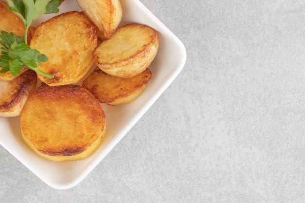 Scheiben bratkartoffeln auf weißem teller. Kostenlose Fotos