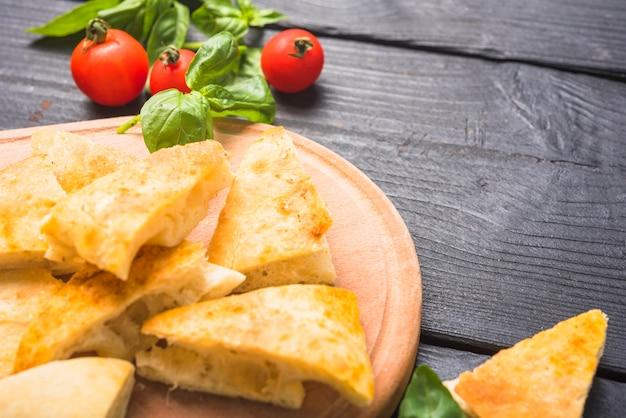 Scheiben brot mit basilikumblättern und -tomaten auf holztisch