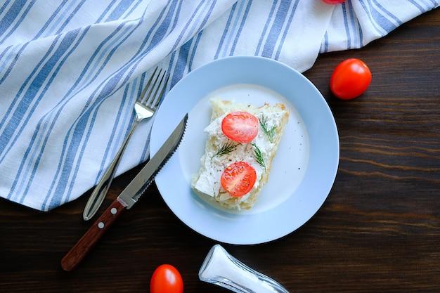 Scheiben brot, sandwiche, rote tomaten, käse, grüns auf einer platte gegen einen holztisch.