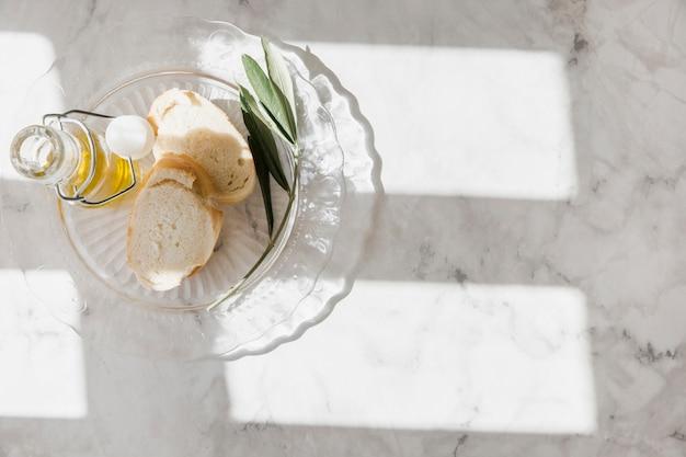 Scheiben der brot- und olivenölflasche auf glasplatte über dem marmorhintergrund