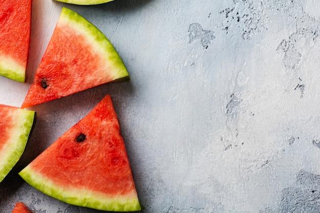 Scheiben der frischen wassermelone mit eis auf einem blauen beton