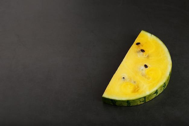 Scheiben der gelben wassermelone auf dunkelheit