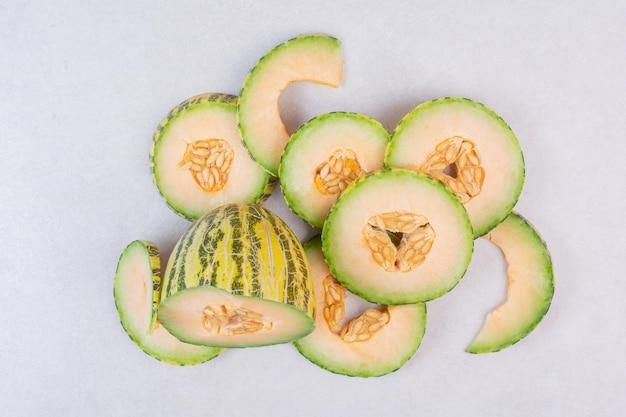 Scheiben der grünen melone auf weißem tisch.