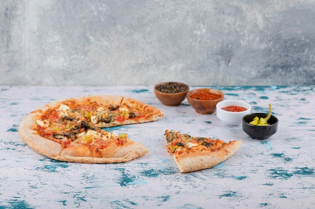 Scheiben der heißen pizza mit pfefferkörnern und pfefferpulver auf einem marmorhintergrund.