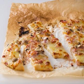 Scheiben der pizza auf pergamentpapier gegen weißen hintergrund