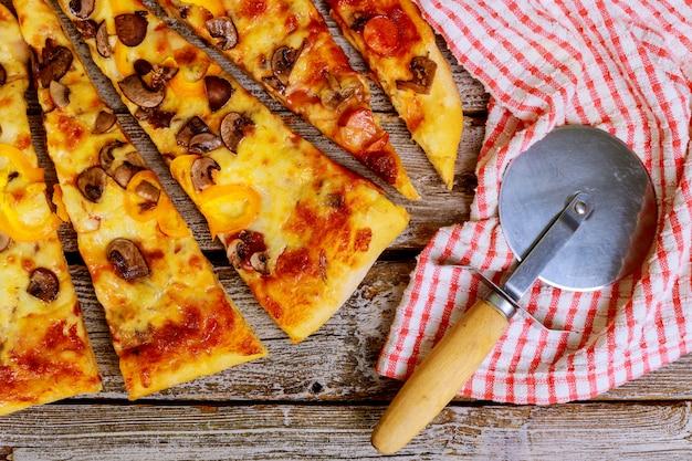 Scheiben der pizza mit verschiedenen belägen auf einem hölzernen hintergrund