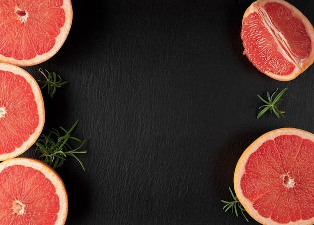 Scheiben der reifen grapefruit auf einem schwarzen steinhintergrund.