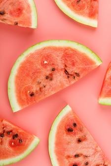 Scheiben der roten wassermelone auf rosa hintergrund in der form.