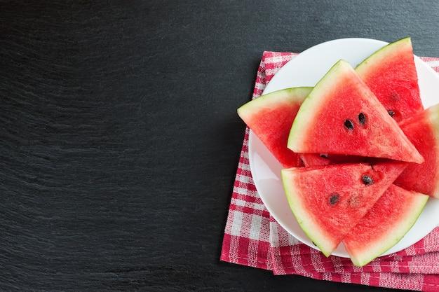Scheiben der wassermelone auf dem teller auf schwarzem schieferhintergrund. draufsicht, flach mit kopierraum liegen