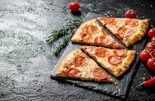 Scheiben duftende peperoni-pizza auf einem steinbrett auf schwarzem rustikalem tisch.