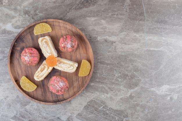 Scheiben einer kuchenrolle, geleebonbons und ein kleiner kuchen auf einem holztablett auf marmoroberfläche