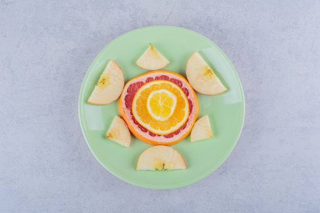 Scheiben frische grapefruit, orange, zitrone und apfel auf grünem teller.