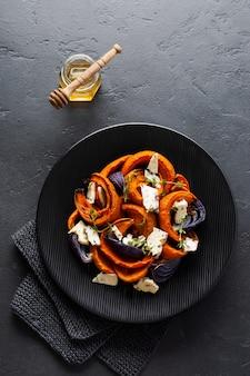 Scheiben gebackener kürbis, zwiebeln, knoblauch, gewürze und käsescheiben dorblu auf schwarzer keramikplatte und altem schwarzem steinhintergrund. ansicht von oben