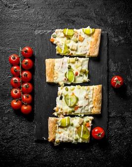 Scheiben gemüsepizza auf einem schneidebrett mit tomaten auf einem zweig.