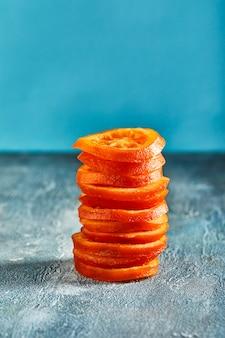 Scheiben getrockneter orangen oder mandarinen an einer blauen wand. vegetarismus und gesunde ernährung. speicherplatz kopieren