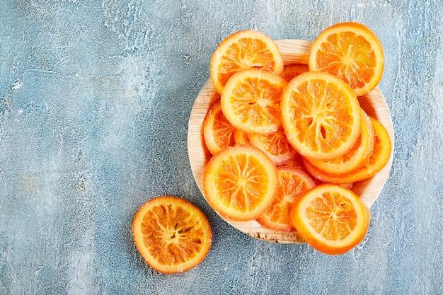 Scheiben getrockneter orangen oder mandarinen in einem holzteller an einer blauen wand. vegetarismus und gesunde ernährung. speicherplatz kopieren. flach liegen