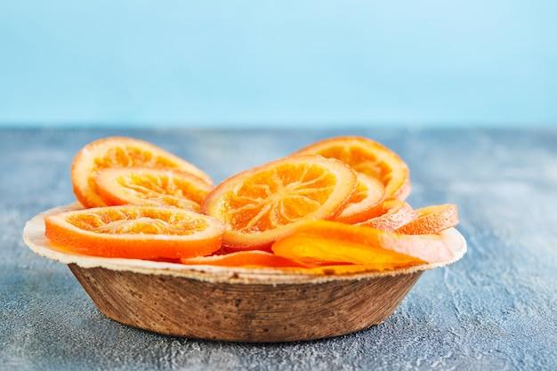 Scheiben getrockneter orangen oder mandarinen in einem holzteller. vegetarismus und gesunde ernährung.