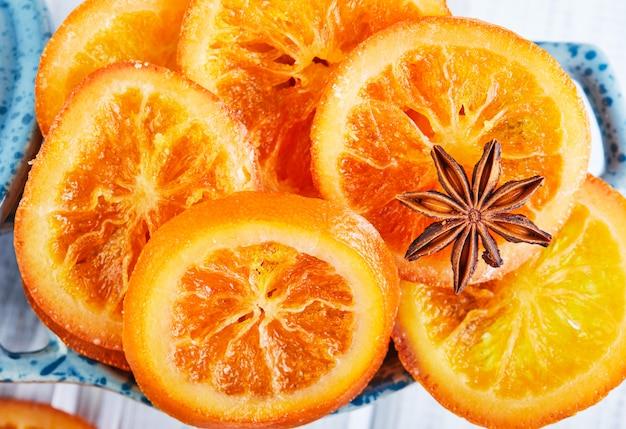Scheiben getrockneter orangen oder mandarinen mit anis und zimt in einer blauen schüssel. vegetarismus und gesunde ernährung