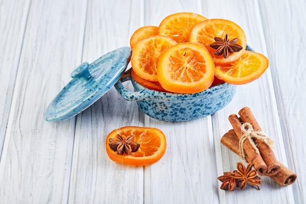 Scheiben getrockneter orangen oder mandarinen mit anis und zimt in einer blauen schüssel vegetarismus und gesunde ernährung