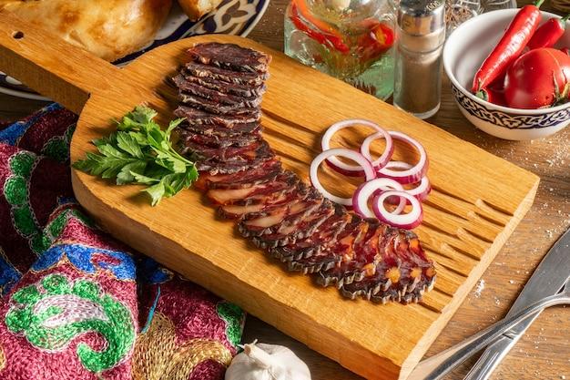 Scheiben hausgemachte getrocknete pferdefleischwurst mit koriander und roten zwiebeln, in scheiben geschnitten und auf einem hölzernen schneidebrett serviert