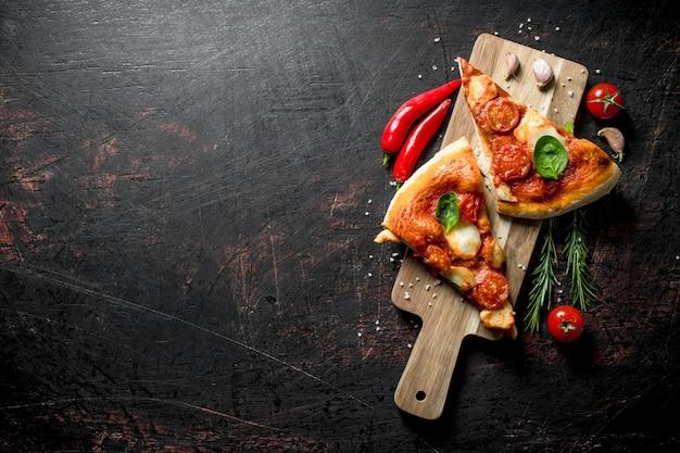 Scheiben hausgemachte pizza auf einem schneidebrett mit chili, tomaten und rosmarin.