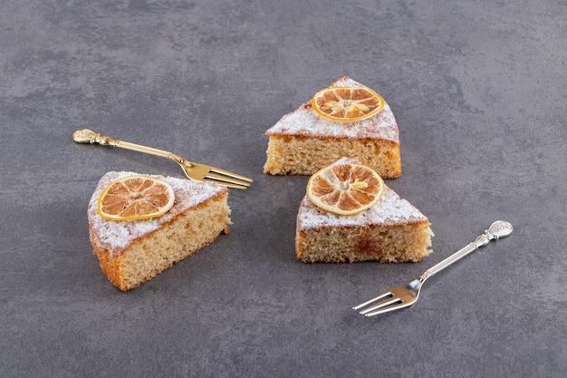 Scheiben hausgemachten kuchens mit zitronen auf steintisch gelegt.