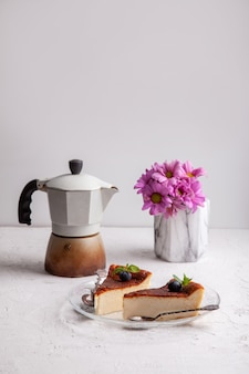 Scheiben hausgemachter baskischer gebrannter käsekuchen mit blaubeeren und minzblättern, geysir-kaffeemaschine, blumen in einer vase