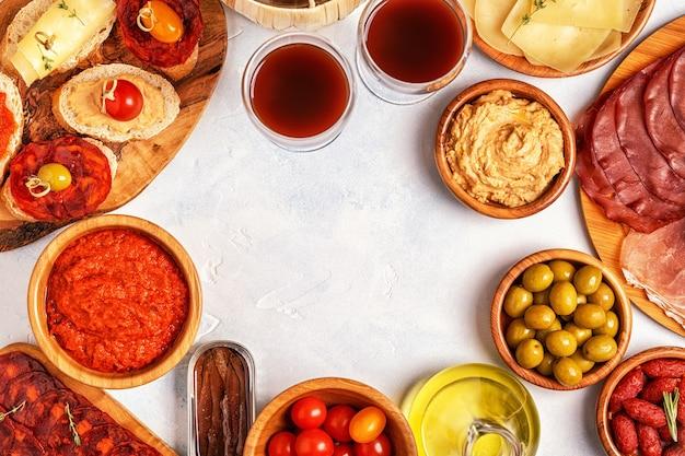 Scheiben jamon, chorizo, wurst, schalen mit oliven, tomaten, sardellen, kichererbsenpüree, käse.