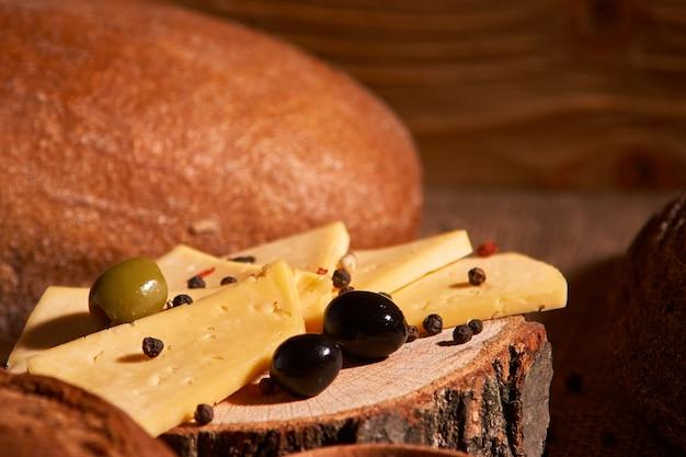 Scheiben käse auf hölzernem schreibtisch zwischen verschiedenen broten