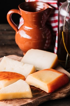 Scheiben käse in der nähe von krug und öl