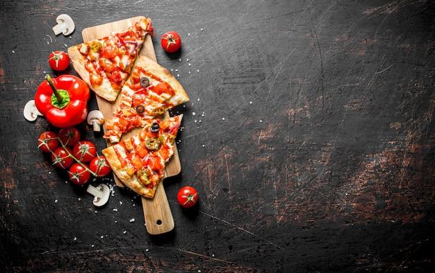 Scheiben mexikanische pizza mit paprika und tomaten auf dunklem rustikalem tisch