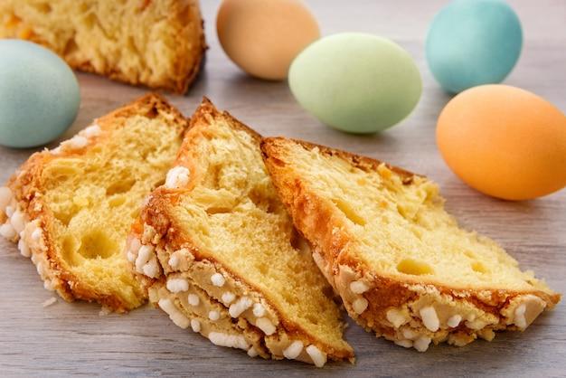 Scheiben osterkuchen und bunte eier sind auf einer hölzernen tischplatte.