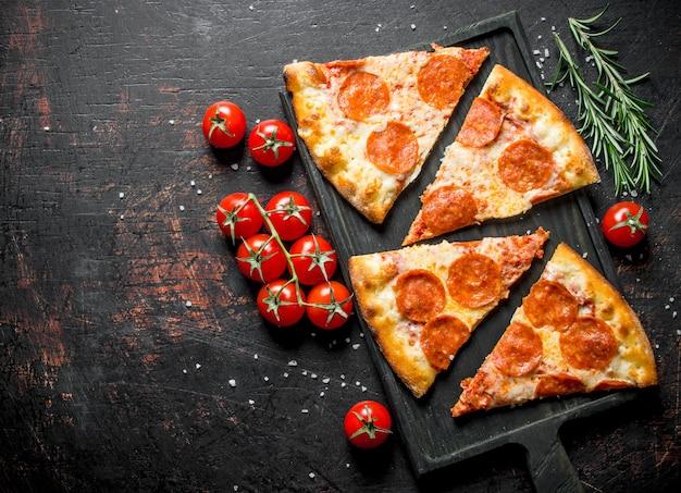 Scheiben peperoni-pizza mit tomaten und rosmarin. auf dunklem rustikalem hintergrund