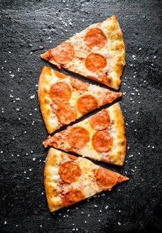 Scheiben peperoni-pizza mit würstchen und käse. auf schwarzer rustikaler oberfläche