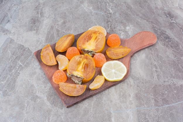 Scheiben persimone, zitrone, mandarine und süßigkeiten an bord.