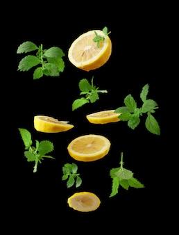 Scheiben reifer saftiger gelber zitronen und minzzweige mit grünen blättern schweben in der luft auf schwarzem grund