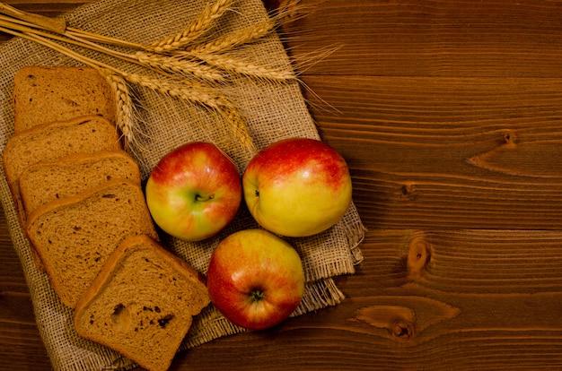 Scheiben roggenbrot, drei äpfel, ohren des weizens auf dem rausschmiß, holztisch, draufsicht