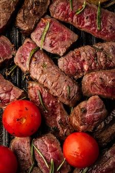 Scheiben saftiges steak mit kirschtomaten auf grillpfanne.