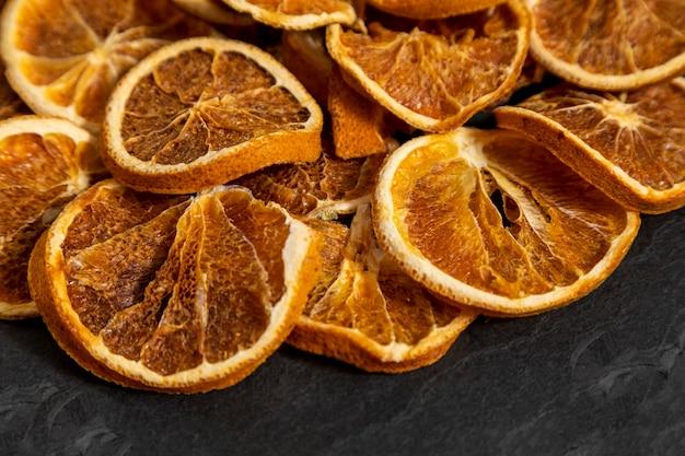 Scheiben von dehydrierter orange auf schwarzem stein. selektiver fokus.