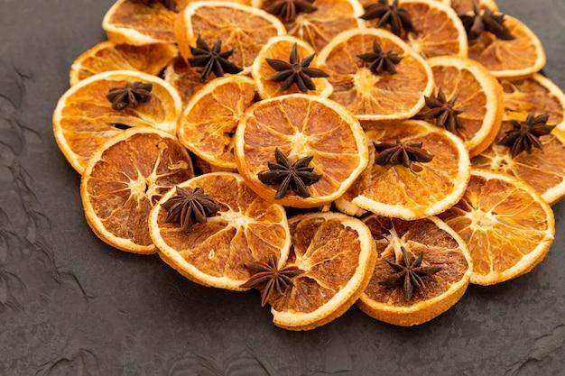 Scheiben von dehydrierter orange und sternanis auf schwarzem stein. selektiver fokus.