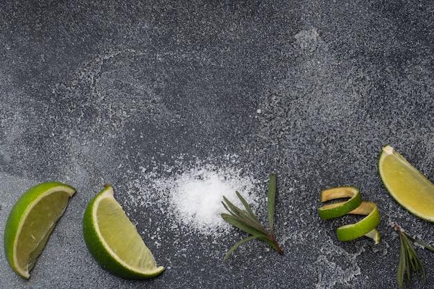 Scheiben von frischem kalk, salz und rosmarin dunklem betonhintergrund.