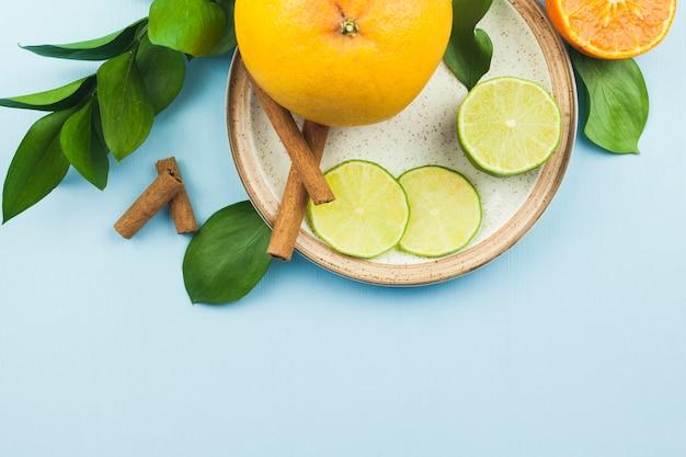 Scheiben von frischen exotischen früchten nahe zimt auf platte mit laub