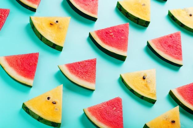 Scheiben von frischen scheiben der gelben und roten wassermelone auf blau.