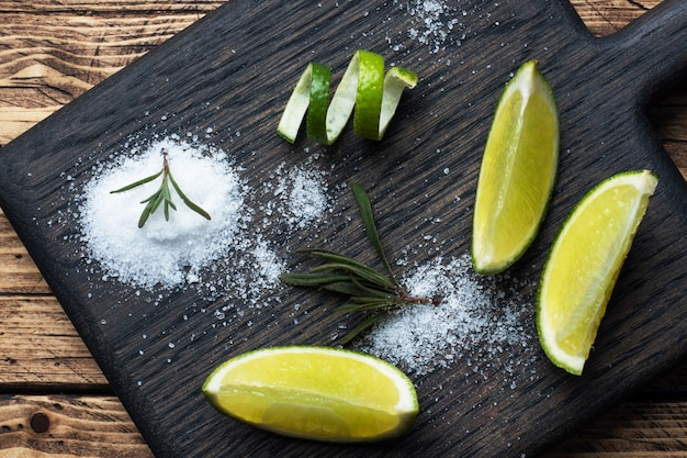 Scheiben von frischer limette, salz und rosmarin auf einem holzschneidebrett.