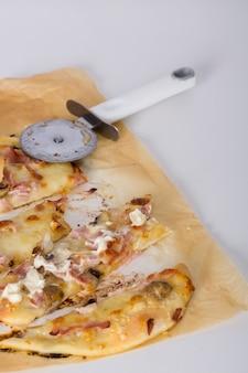 Scheiben von gebackener pizza mit cutter auf pergamentpapier