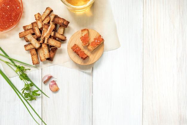 Scheiben von gebratenen croutons mit sauerrahmsauce, kaviar und knoblauchzehen hautnah auf einem weißen holzbrett draufsicht mit kopierraum