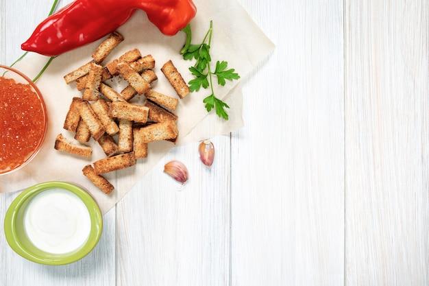 Scheiben von gebratenen croutons mit sauerrahmsauce paprikakaviar und knoblauchzehen hautnah auf einem weißen holzbrett white