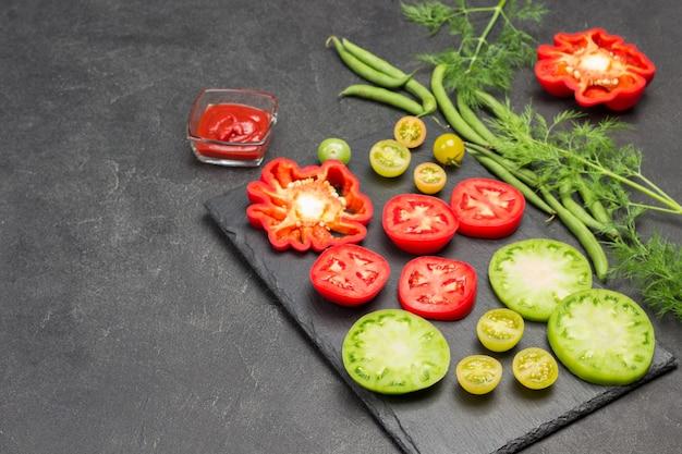 Scheiben von grünen und roten tomaten auf schneidebrett. grüne bohnen und dill auf dem tisch. platz kopieren. schwarzer hintergrund. flach legen