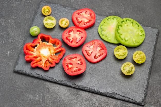 Scheiben von grünen und roten tomaten auf schneidebrett. platz kopieren. schwarzer hintergrund. flach legen