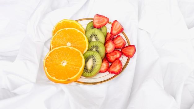 Scheiben von orangen, kiwi und erdbeeren auf platte
